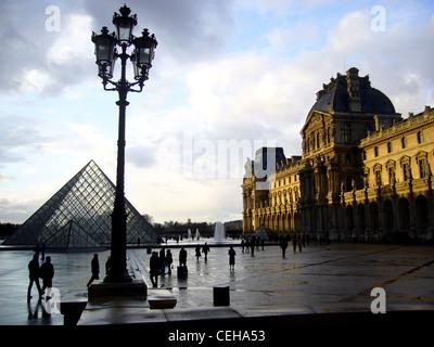 Silhouetten an einem regnerischen Tag in Place du Carrousel du Louvre, Paris, Frankreich - Stockfoto