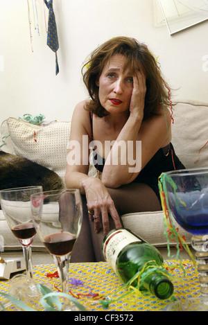 Weibliche brünette Haare trägt schwarzes Kleid sitzt am Rand des Sofa gelehnt vorwärts Hand Kopf suchen Elend umgeben - Stockfoto