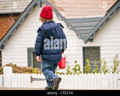 Kleines Kind zu Fuß entlang einer Wand mit einem Eimer und roten Hut in Whitstable, Kent, Großbritannien. - Stockfoto