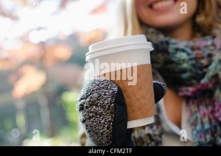 USA, Staat New York, Brooklyn, New York City Frau Handschuhe halten Kaffeetasse - Stockfoto