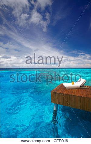 Sonnenliege und Steg in der blauen Lagune, Malediven, Indischer Ozean, Asien - Stockfoto