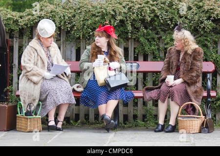 drei ältere Damen sitzen auf einer Bank an einem 40er Jahre während des Krieges Wochenende auf der East Lancs Railway - Stockfoto