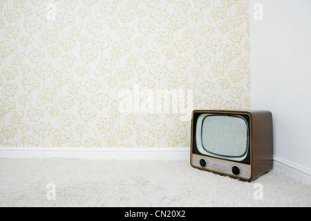 Retro-Fernseher in der Ecke des Raumes mit gemusterten Tapeten - Stockfoto