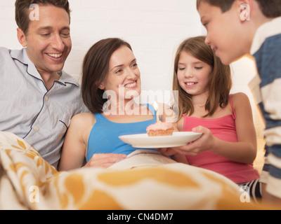 Mitte Erwachsene Frau empfangen Geburtstagskuchen im Bett von Familie - Stockfoto