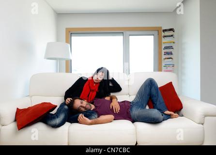 Junges Paar zu Hause im Wohnzimmer sitzt auf einem weißen sofa - Stockfoto
