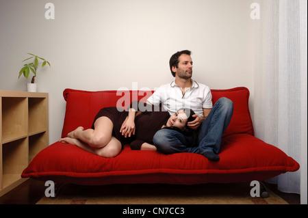 Junges Paar sitzt auf einem roten Sofa im Wohnzimmer - Stockfoto
