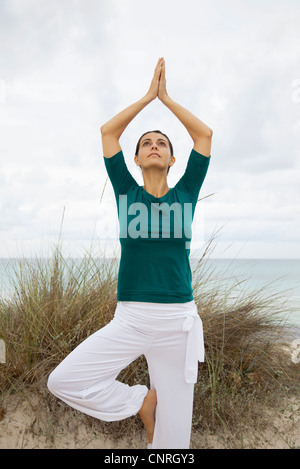 Reife Frau in Baumpose am Strand, Porträt - Stockfoto