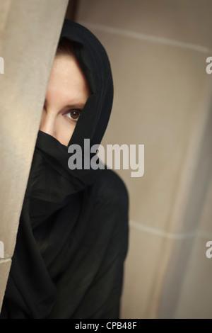 Vorsichtige islamische Frau in einer Fensterscheibe, die traditionelle Burka oder Niqab tragen. - Stockfoto
