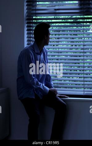 Junger Mann sitzt in einem dunklen Raum mit Blick durch ein Fenster Blind. - Stockfoto