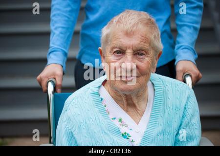 Senior-Frau im Rollstuhl mit Assistent hinter ihr. - Stockfoto