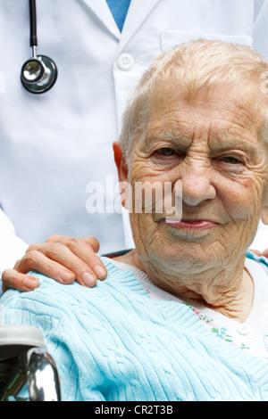 Senior-Frau im Rollstuhl mit Arzt hinter ihr - Stockfoto