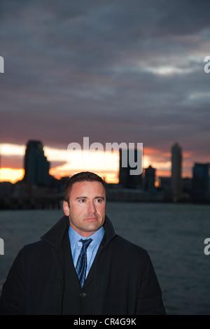 Porträt des kaukasischen Mann in Anzug mit Mantel auf den Straßen von New York City Amerika bei Sonnenuntergang - Stockfoto
