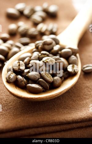 Kaffeebohnen in Holzlöffel auf braunem Tuch - Stockfoto