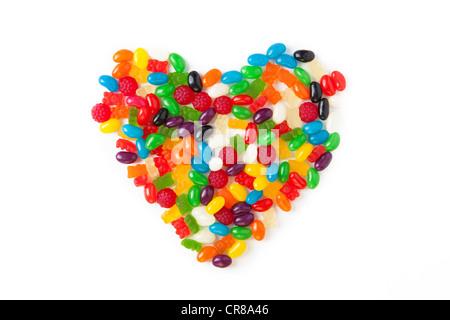 Bunten Süßigkeiten in Form eines Herzens auf einem weißen Hintergrund angeordnet - Stockfoto