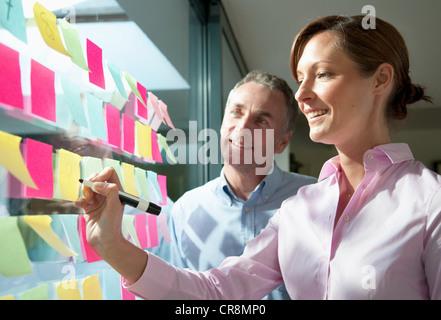 Zwei Geschäftsleute auf selbstklebende Hinweise zum Fenster schreiben - Stockfoto