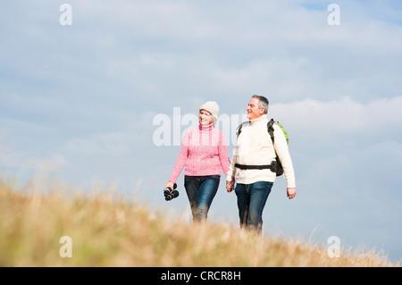 Paare, die Hand in Hand in Wiese - Stockfoto