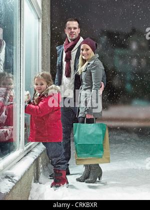 Familie Weihnachtseinkäufe im Schnee - Stockfoto