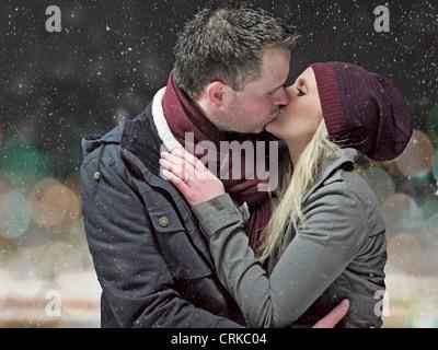 Paar küssen im Schnee in der Nacht - Stockfoto