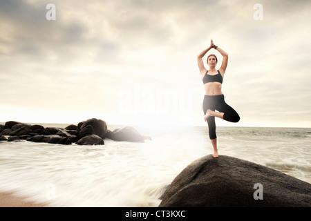 Frau praktizieren Yoga auf Felsen am Strand - Stockfoto