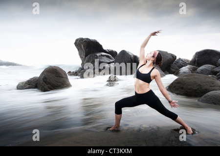 Frau praktizieren Yoga am Sandstrand - Stockfoto
