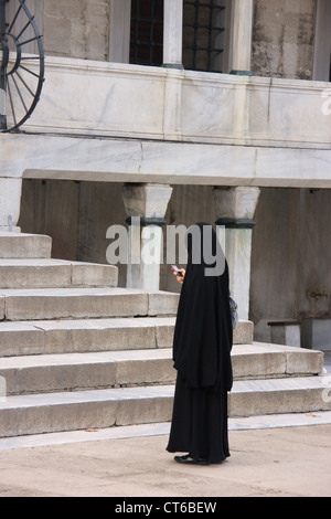 Die muslimische Frau im schwarzen Tschador mit Handy, Innenhof des Sultan Ahmed Mosque, Sultanahmet, Istanbul, Türkei - Stockfoto