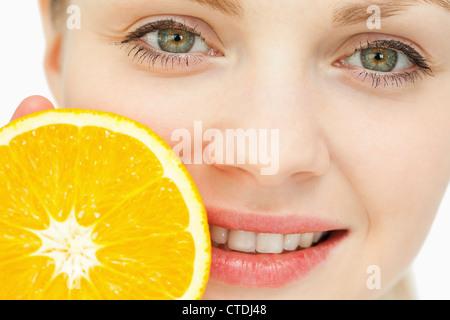 Nahaufnahme einer Frau platzieren eine Orange in der Nähe von ihren Lippen - Stockfoto