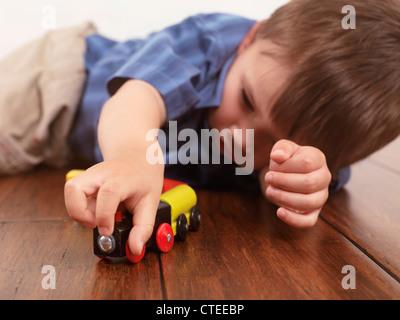 Junge spielt mit einer Spielzeugeisenbahn auf Hartholz-Fußboden liegend - Stockfoto