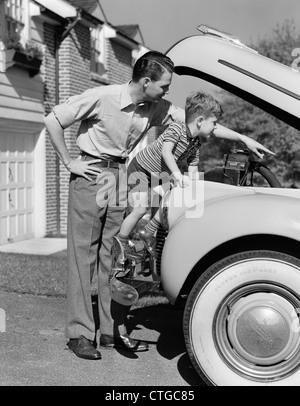 1940ER JAHREN VATER & SOHN ÜBERPRÜFUNG UNTER HAUBE DES AUTOS IN DER EINFAHRT - Stockfoto
