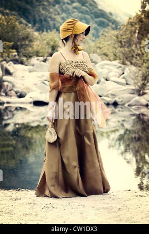 eine junge Frau in einem Zeitraum Kleid stehen am Ufer eines Sees - Stockfoto