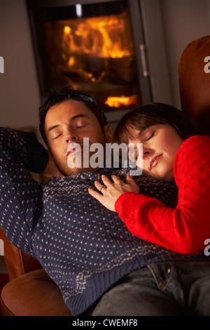 Applying paar kuscheln auf Sofa gemütliche Kaminfeuer - Stockfoto