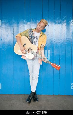 Porträt von einem trendigen Teenager Gitarre Holz vertäfelten Wand - Stockfoto