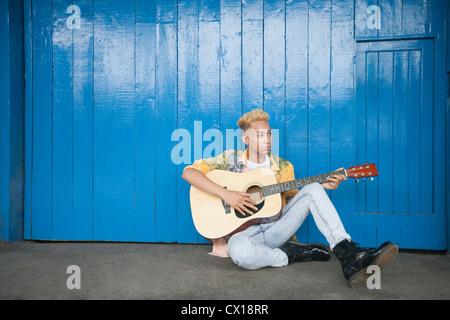 Trendige Teenager, Gitarre zu spielen, als er gegen Holz vertäfelten Wand sitzt - Stockfoto