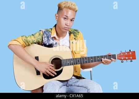 Porträt eines jungen Teenager Gitarre auf blauem Hintergrund - Stockfoto