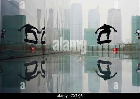 Ein Skateboarder mitten in der Luft in der Innenstadt - Stockfoto