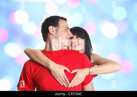 Junges Paar umarmt und bilden eine herzförmige Geste mit den Händen - Stockfoto