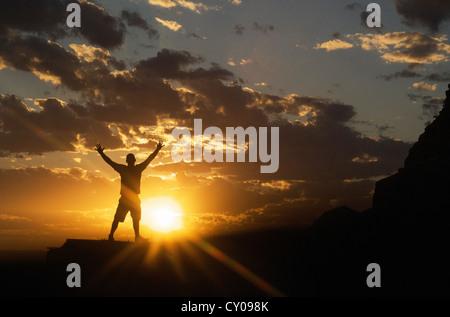 Männliche Figur mit Armen ausgestreckt stehend mit Sonnenuntergang im Hintergrund - Stockfoto