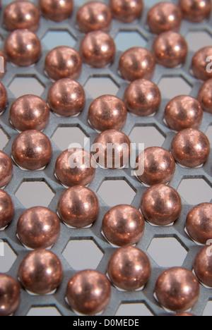 kleine metallische Kugeln in metallischen Wabenmuster - Stockfoto
