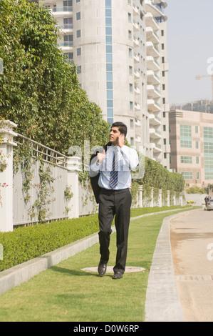 Unternehmer sprechen über ein Mobiltelefon auf einem Bürgersteig, Gurgaon, Haryana, Indien - Stockfoto