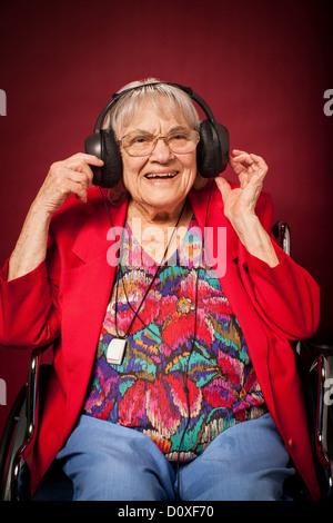 Ältere Frau, die Musik über Kopfhörer hören - Stockfoto