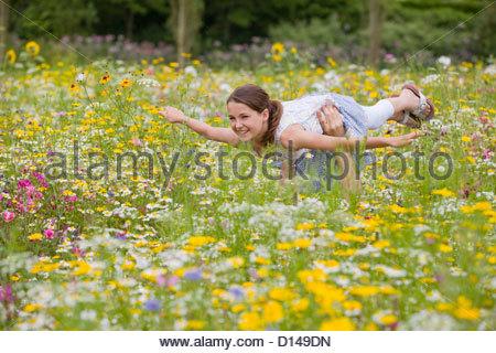 Vater Holding fliegende Mädchen unter Wildblumen im sonnigen Wiese - Stockfoto