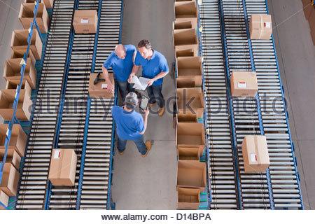 Arbeitnehmer, die unter Boxen auf Förderbändern im Auslieferungslager treffen - Stockfoto