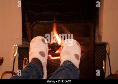Erwärmung Der Füße In Pantoffeln Am Offenen Kamin   Stockfoto