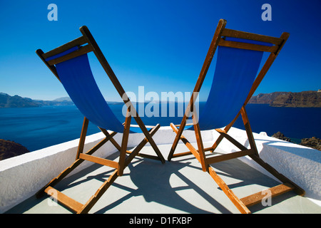 Liegestühle auf der Terrasse mit Blick auf Meer, Santorini, Kykladen, griechische Inseln, Griechenland, Europa - Stockfoto