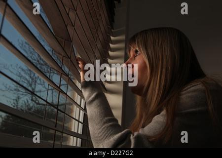 Ängstlich Reife Frau spähte durch Fenster-Vorhänge in der Nacht. - Stockfoto