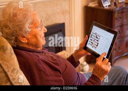 Ältere Frau Rentner mit Brille auf Apple Ipad Tablet zu Hause entspannen und tun Kreuzworträtsel Online Zeitung - Stockfoto