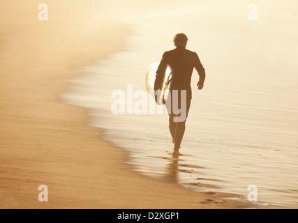 Ältere Surfer tragen Board am Strand - Stockfoto