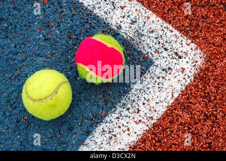 Tennis, die farbigen Kugeln in der Ecke eines synthetischen Feldes platziert. - Stockfoto