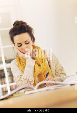 Beschäftigt College-Studentin in der Bibliothek, die Überprüfung ihrer Lektionen für die Prüfung - Stockfoto