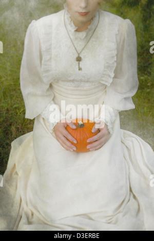 eine Frau in einem viktorianischen Kleid sitzt auf dem Rasen und hält einen Kürbis auf dem Schoß - Stockfoto