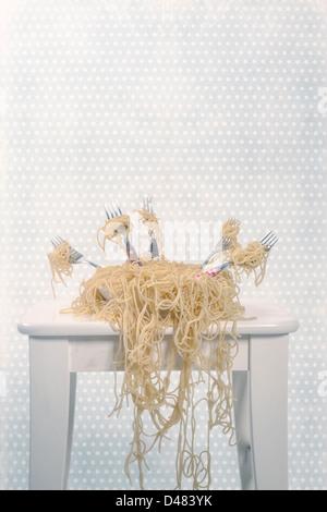 ein Teller voll Spaghetti mit fünf Gabeln - Stockfoto